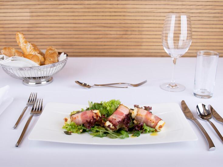 Patroskäse im Speckmantel auf Blattsalat und Pinienkernen